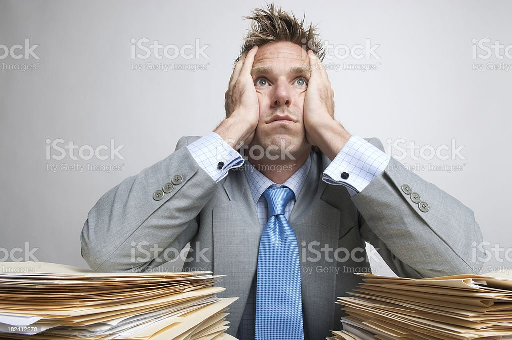Businessman Office Worker Looks Dazed Bored above Piles of Paperwork royalty-free stock photo