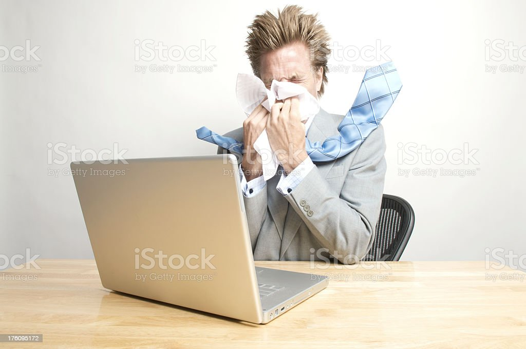 Businessman Office Worker Sneezing Big at his Desk royalty-free stock photo