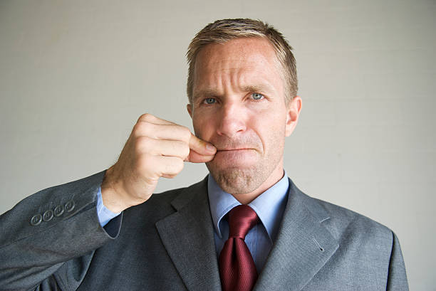Businessman Office Worker Zips His Mouth to Keep Secret Businessman looks at the camera with a serious face as he zips his mouth closed finger on lips stock pictures, royalty-free photos & images