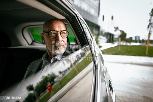 Handsome senior businessman on a back seat of taxi car, looking through the window