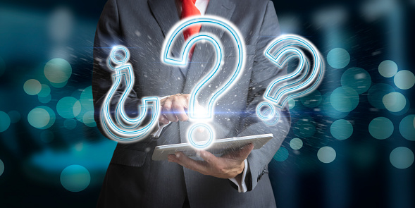 Businessman on a dark background with tablet and with question marks as a concept of doubt and thinking.