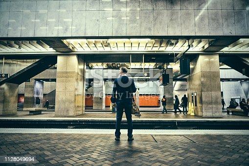 Businessman stands by train platform