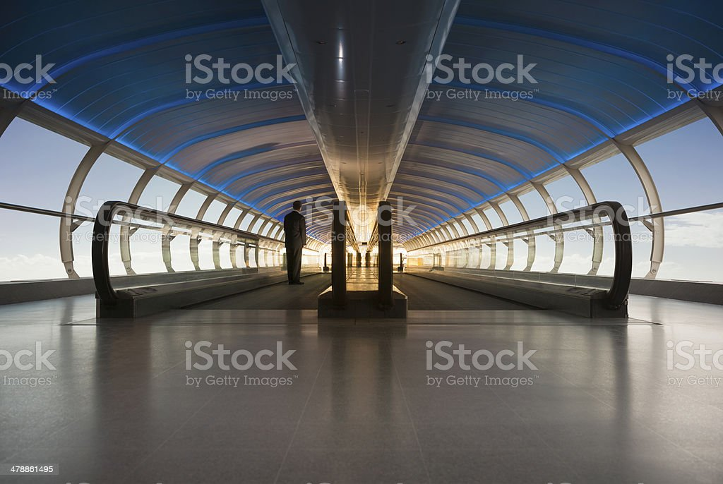 Businessman on a moving walkway heading towards bright sunlight stock photo