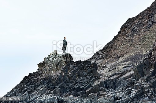 A businessman, holding his briefcase, stands on a rocky slope and looks up at the challenge of an even steeper slope in front of him.