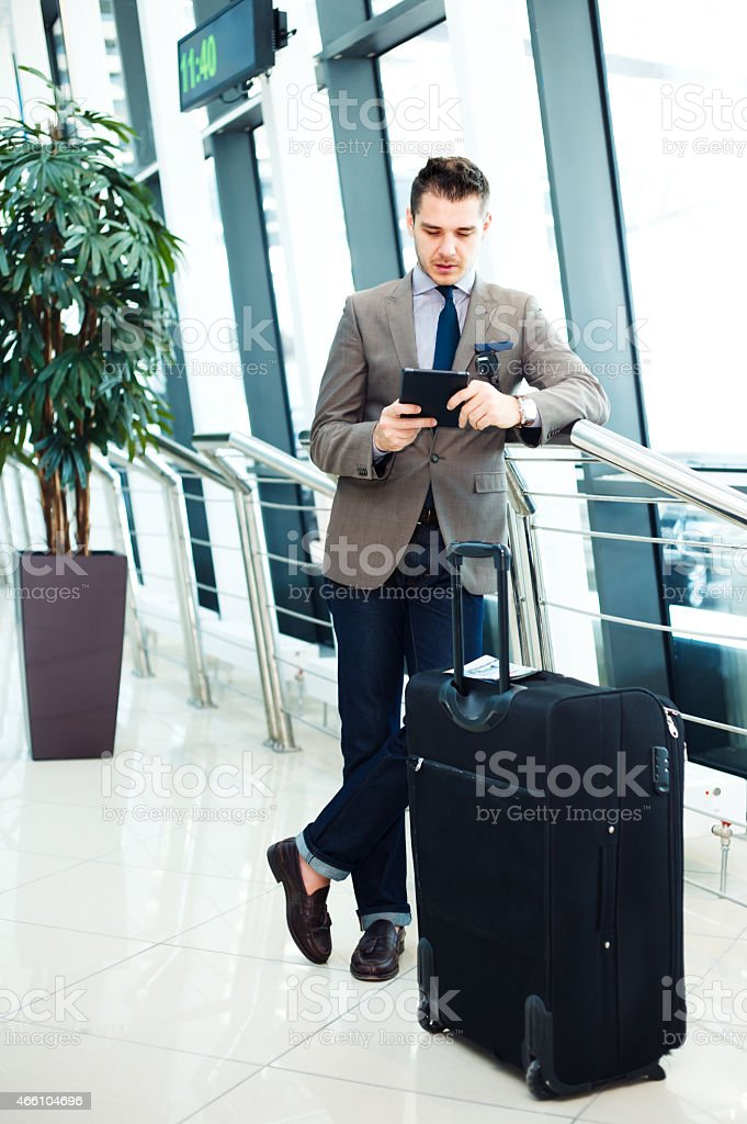 Businessman on a tablet while waiting for his flight stock photo