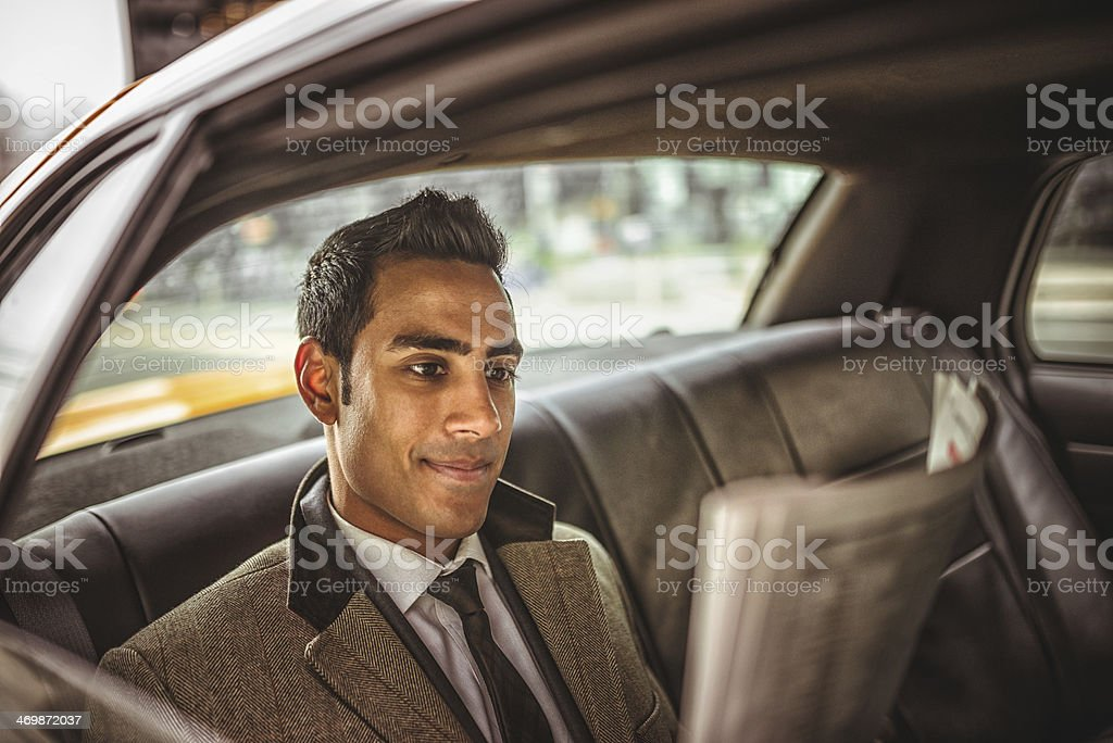 Businessman on a taxi cab reading newspaper stock photo