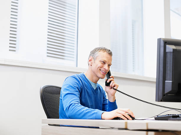 Businessman on a telephone at his computer in an office stock photo