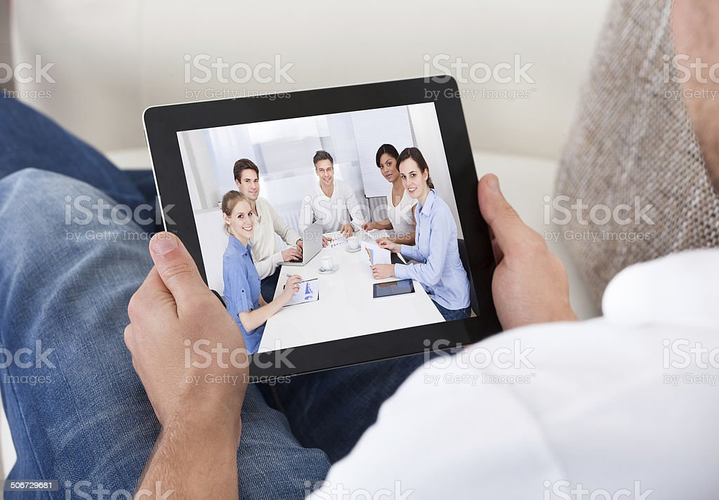 Businessman on a video call chatting to colleagues stock photo