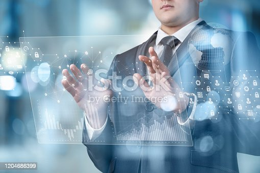 istock Businessman on a virtual screen analyzes financial statistics. 1204686399