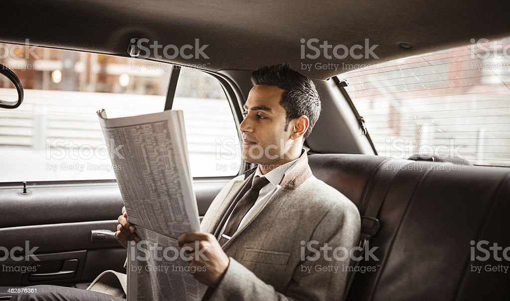 Businessman on a yellow cab reading newspaper stock photo