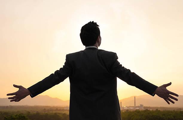 Geschäftsmann auf Ausgestreckte Arme über Sonnenuntergang – Foto