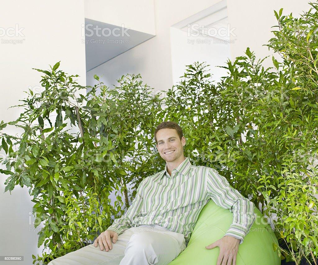 Biznesmen na beanbag otoczony roślin zbiór zdjęć royalty-free