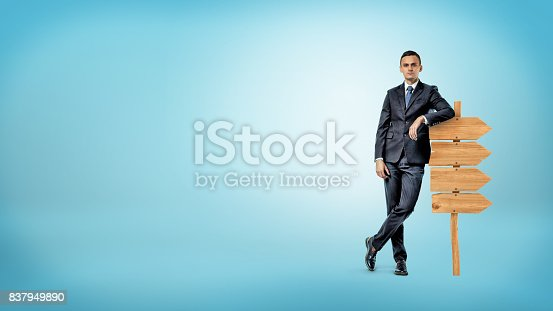 istock A businessman on blue background casually leans on a small wooden signboard showing way in only one direction 837949890