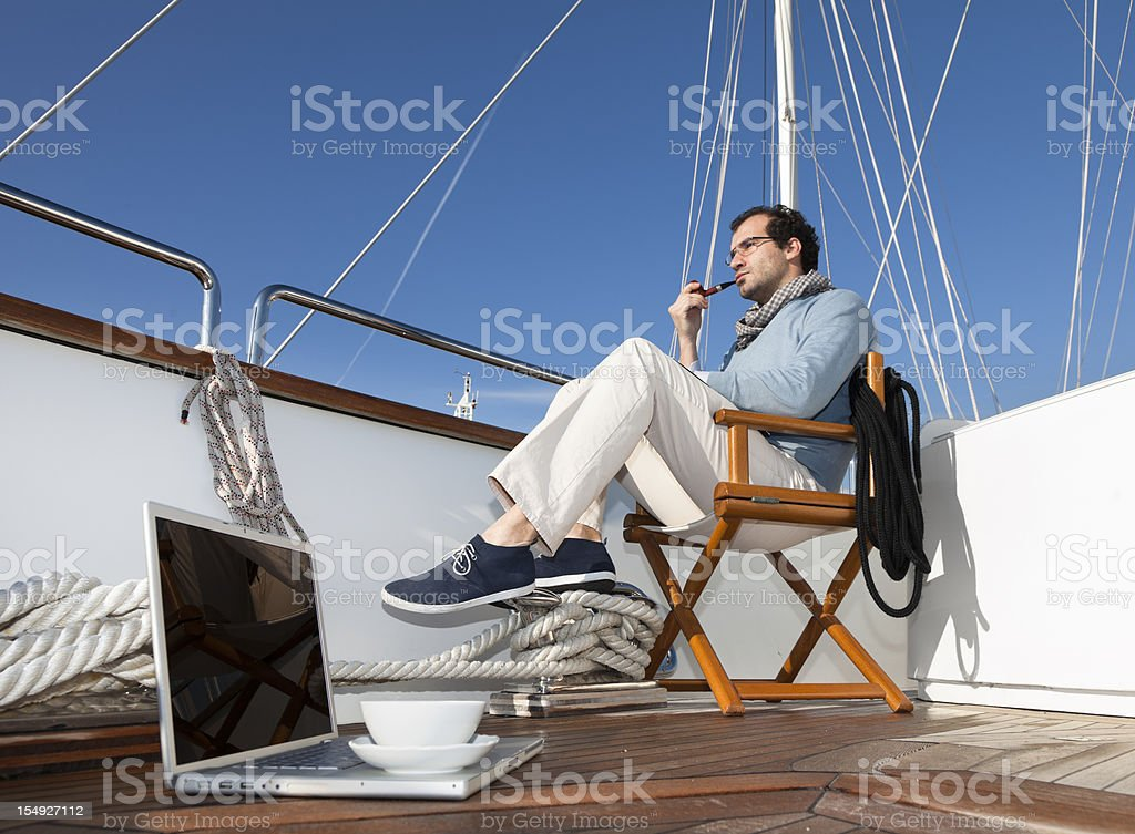Businessman on board of the yacht relaxing smoking pipe royalty-free stock photo