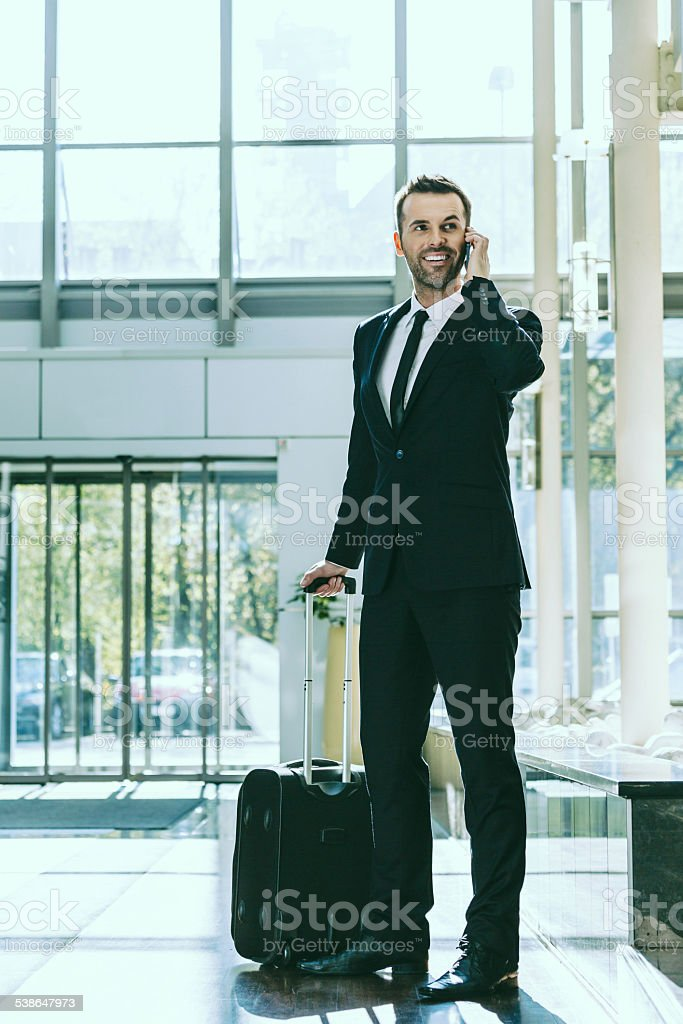 Businessman on business travel in hotel Full lenght portrait of an attractive businessman wearing suit standing in a hotel hall, holding suitcase and talking on mobile phone. 2015 Stock Photo