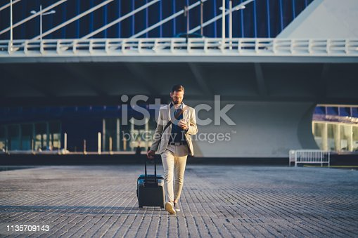 Young businessman with suitcase just arriving in Valencia and texting on phone