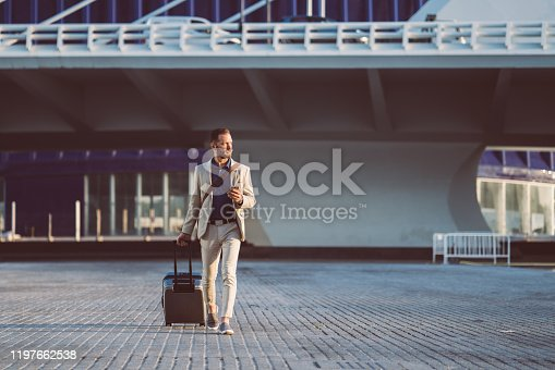Businessman with suitcase just arriving in Valencia and texting on phone