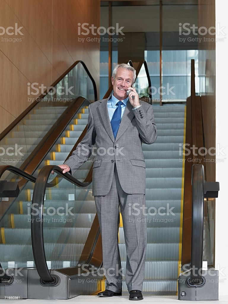 Businessman on cell phone by escalator royalty-free stock photo