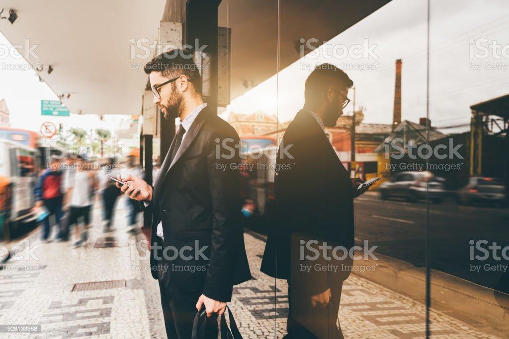 Geschäftsmann auf Stadtstraße in der Nähe von Bushaltestelle mit Handy – Foto