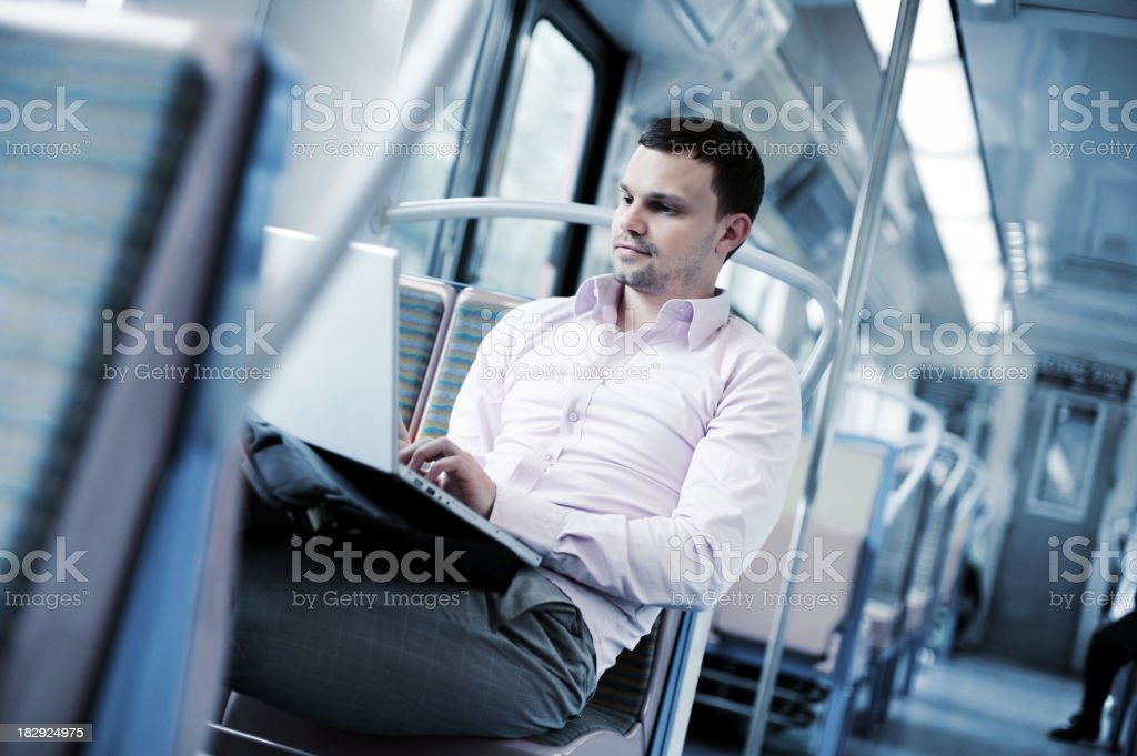Businessman on Commuter Train with Laptop Computer stock photo