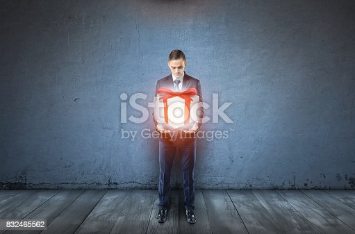 istock A businessman on dark blue background holds a large glowing giftbox 832465562