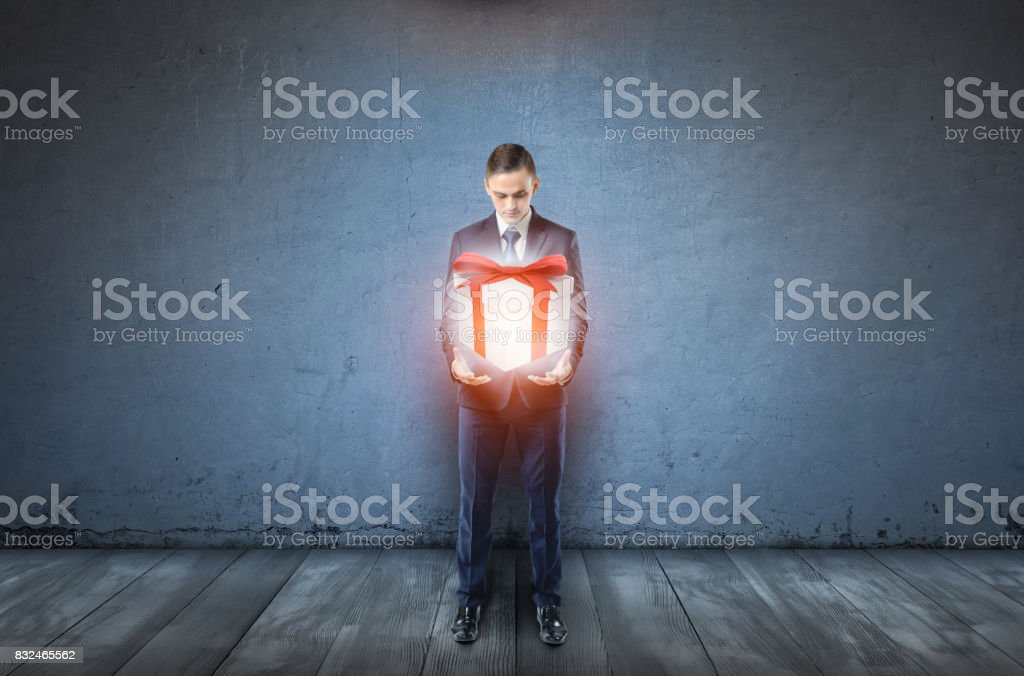 A businessman on dark blue background holds a large glowing giftbox stock photo