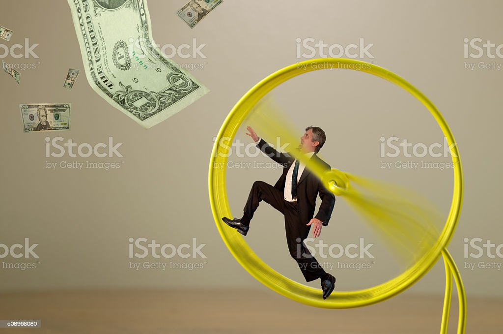 Businessman on hamster wheel chasing money success stock photo