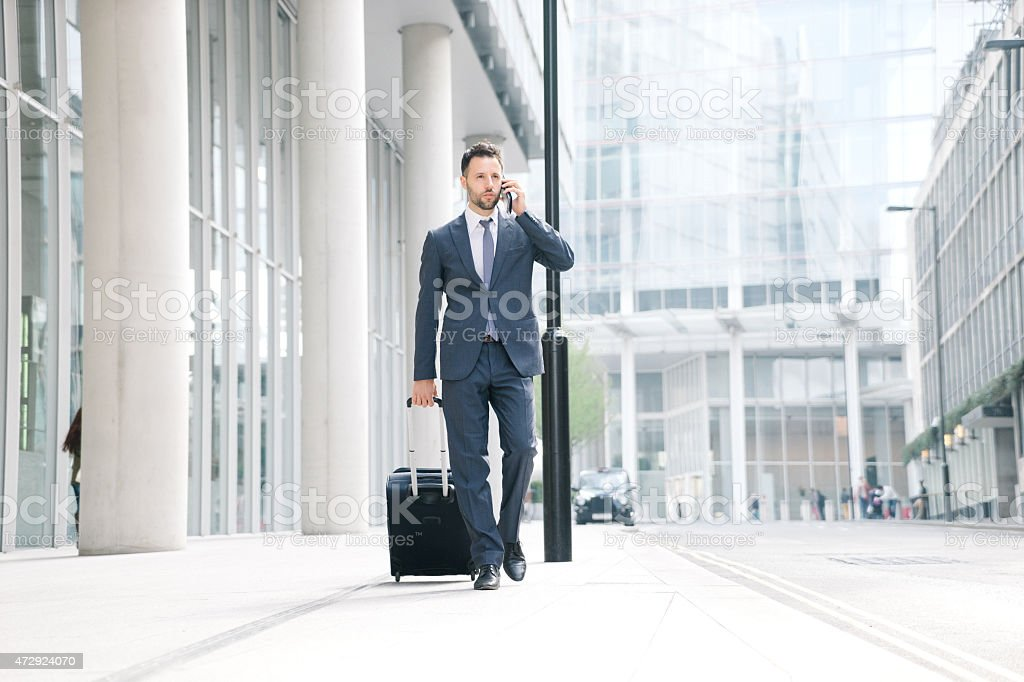 Businessman On His Cell Phone With Suitcase stock photo