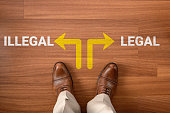istock Businessman on laminate flooring and choose Illegal or Legal, two different ways 1288139335