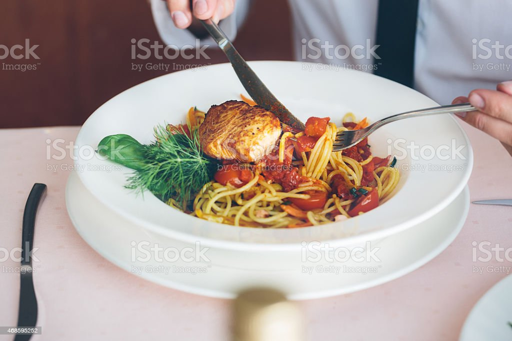 Businessman on lunch break eating pasta Businessman eating pasta at lunch. Close up of meal, plate and cutlery. Unrecognizable person. 2015 Stock Photo