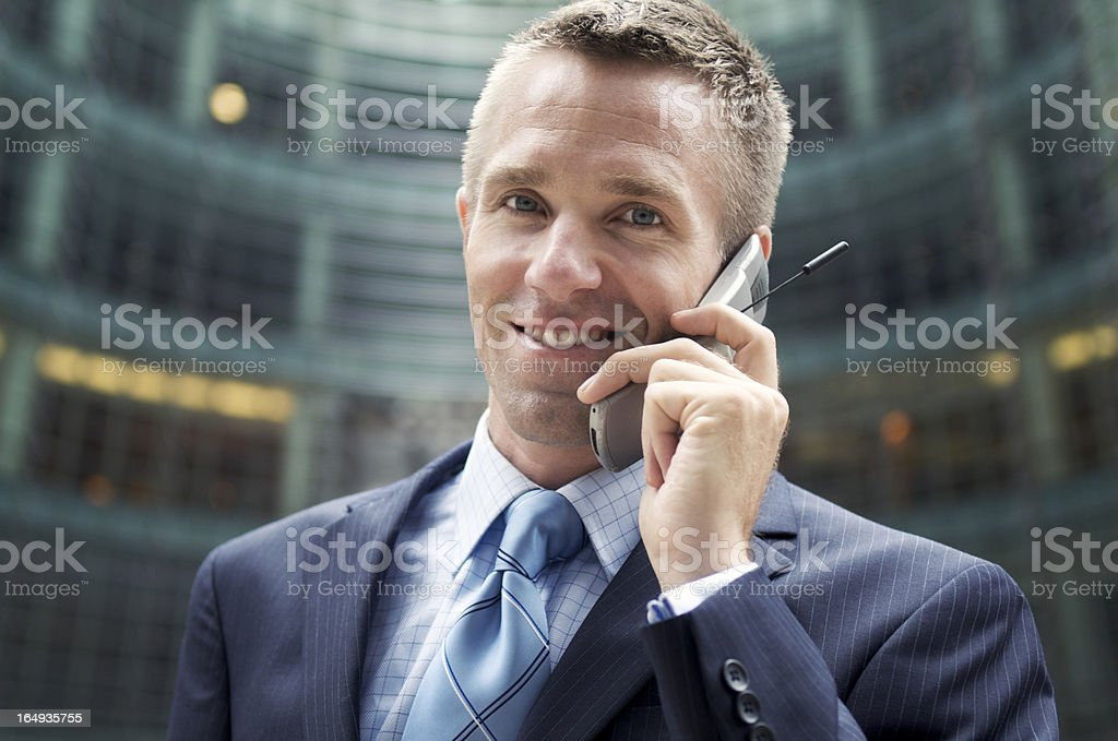 Businessman on Mobile Phone Looks at Camera Smiling stock photo