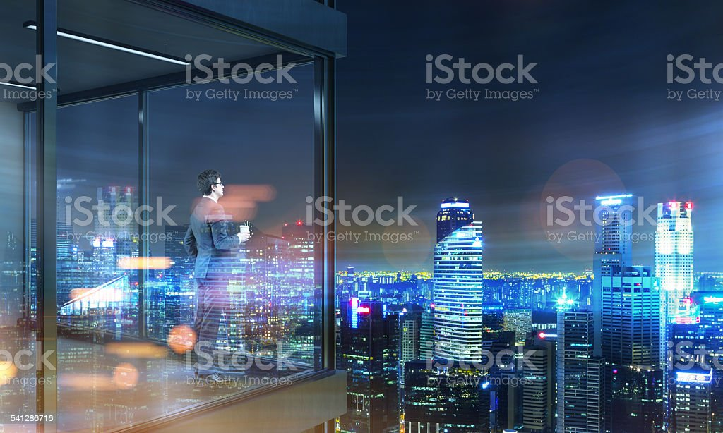 Businessman on panoramic balcony night stock photo