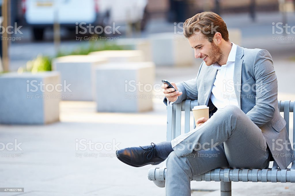 Businessman On Park Bench With Coffee Using Mobile Phone stock photo