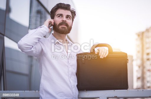 636829300 istock photo Businessman on phone call outdoors 598533348