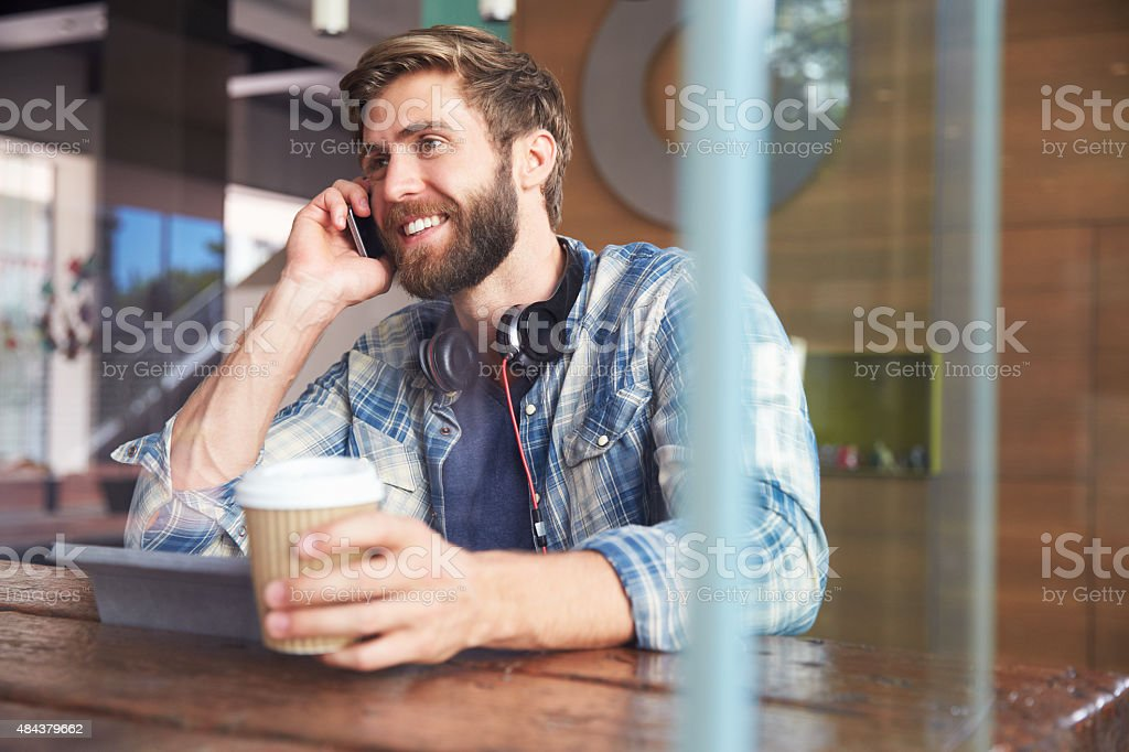 Businessman On Phone Using Digital Tablet In Coffee Shop royalty-free stock photo