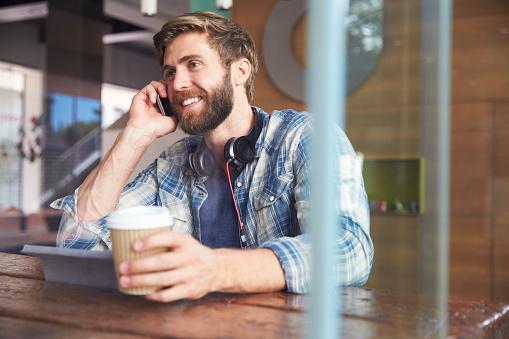 Businessman On Phone Using Digital Tablet In Coffee Shop