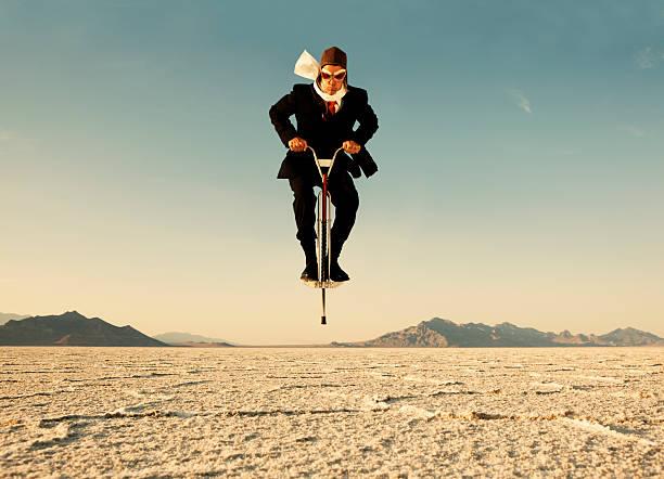 uomo d'affari con pogo nel deserto - molla foto e immagini stock