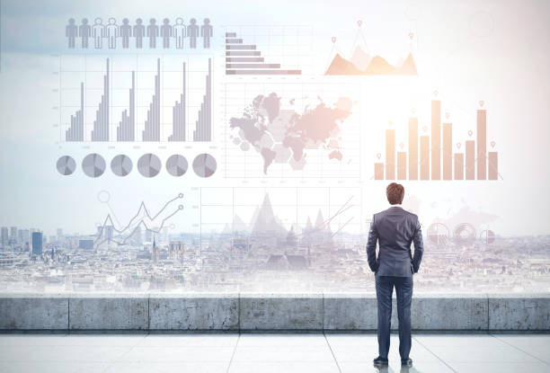 Businessman on roof, graphs and city Rear view of a businessman looking at a gray cityscape in front of him. Gray holograms of graphs in the sky. Elements of this image furnished by NASA. Toned image, double exposure market research stock pictures, royalty-free photos & images