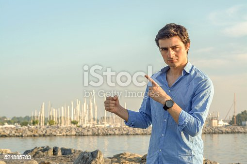 Attractive male looking to the camera with a confident , seriouslook and a marine background
