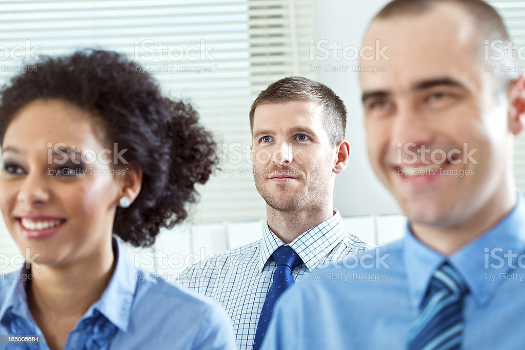 Businessman on seminar Three business people during business conference. Focus on businessman sitting in second row. 25-29 Years Stock Photo