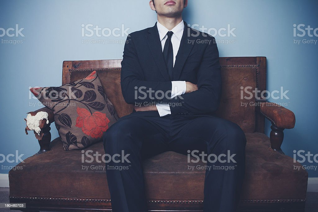 Businessman on sofa in dominant pose royalty-free stock photo