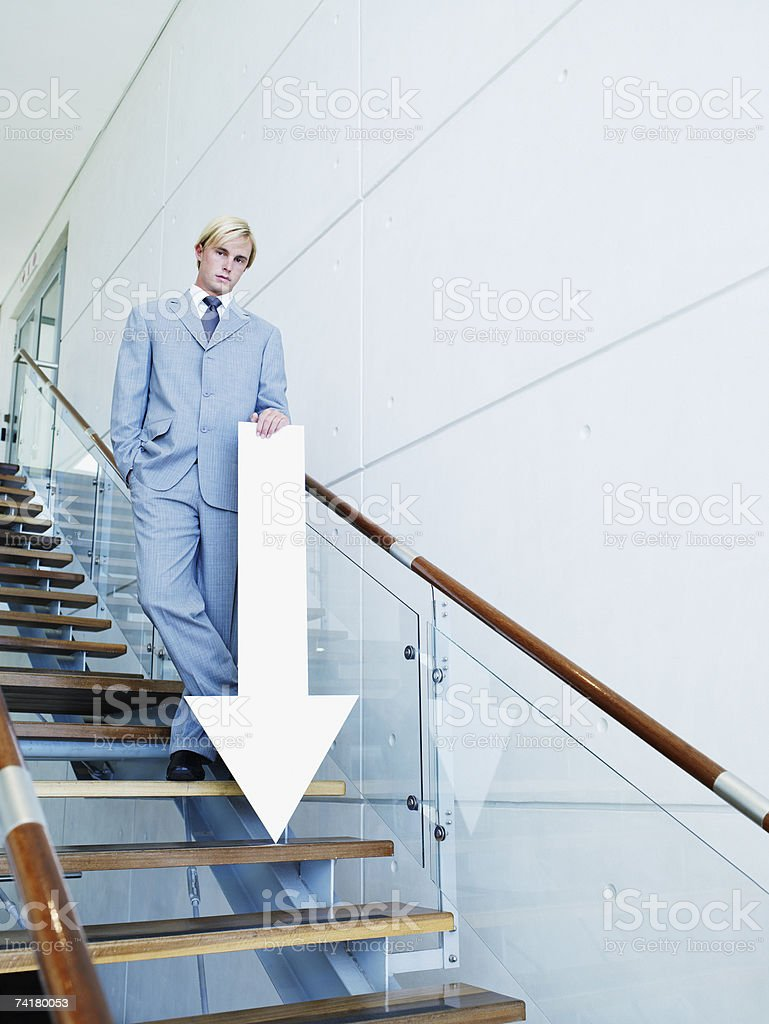 Businessman on stairs with blank arrow pointing down stock photo