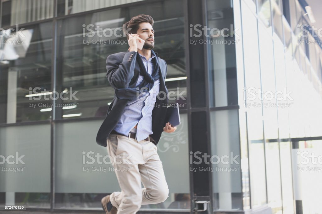 Businessman on street hurry on work and talking on mobile phone. stock photo