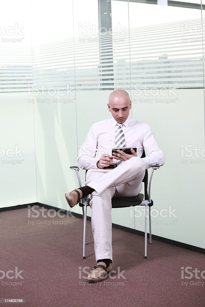Businessman on tablet computer in an empty glass office royalty-free stock photo