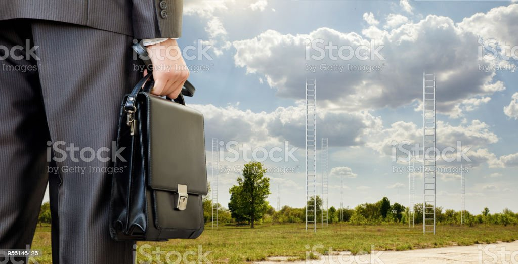 Businessman on the background of stairs into the clouds. stock photo