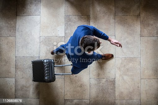 High angle view of an unrecognizable Caucasian businessman with a suitcase traveling - in an airport or a hotel.