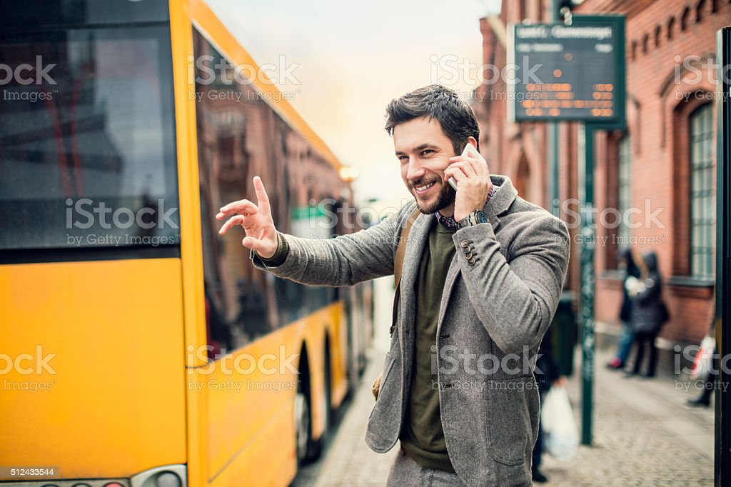 Businessman on the phone at bus station stock photo