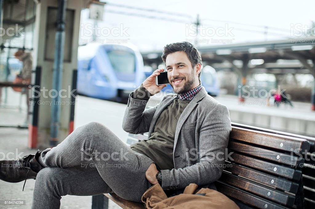 Businessman on the phone at train station stock photo