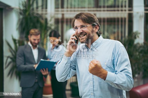 624700110istockphoto Businessman on the phone in office with colleagues in background 1001505930