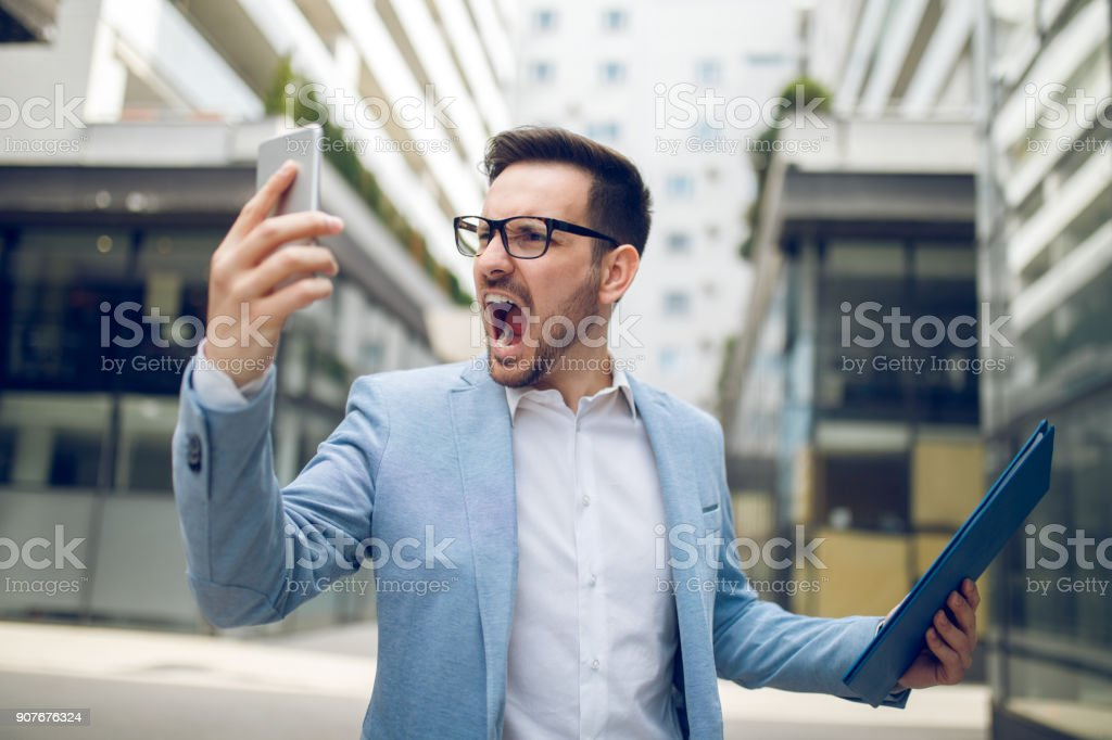 Businessman on the phone shouting stock photo